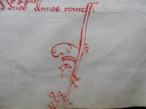 AA7 folio 16 recto : Grotesque terminant la hampe d'une lettre au bas d'une page